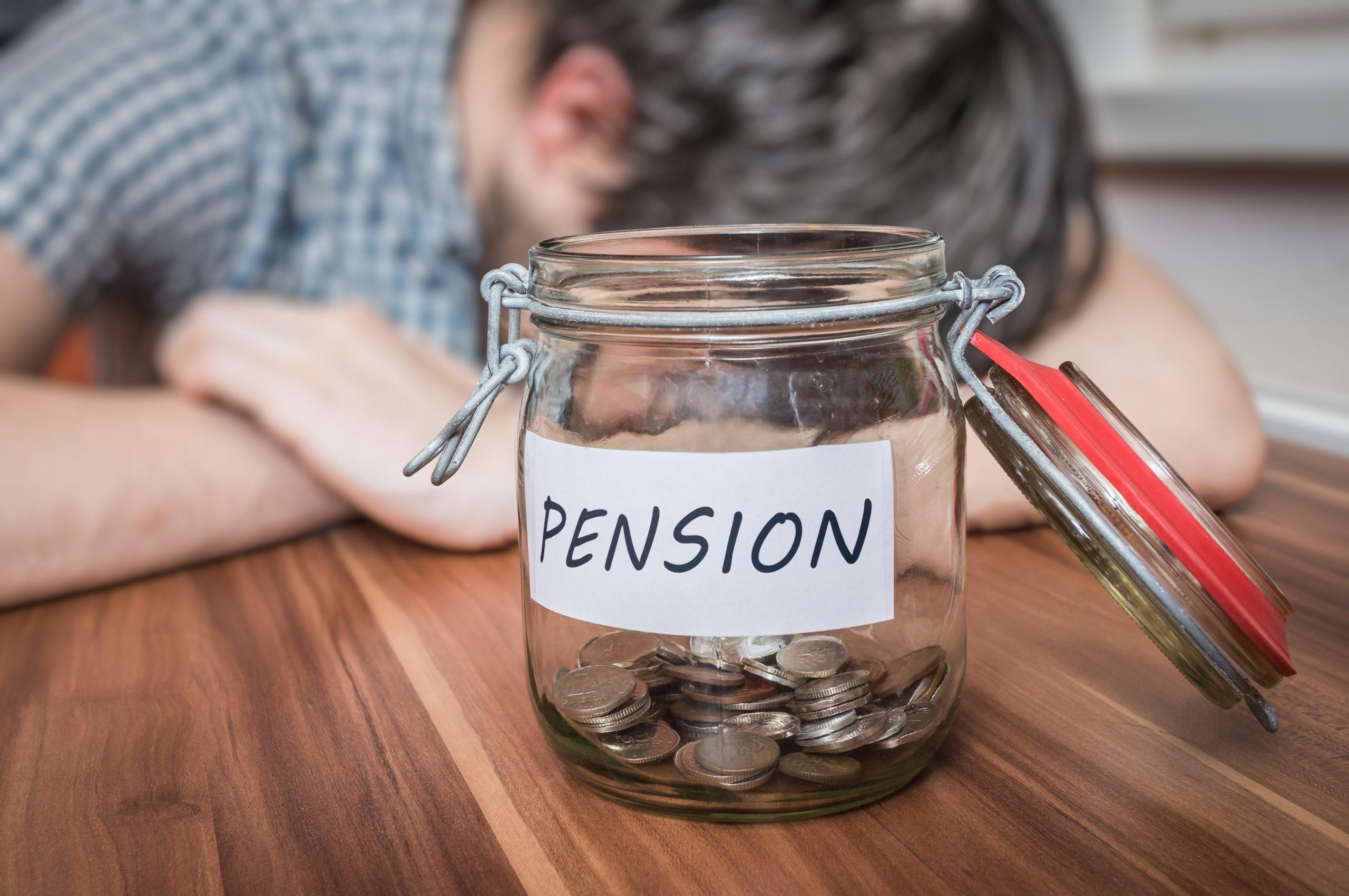 Depressed man lying on table. Pension savings in jar in front.